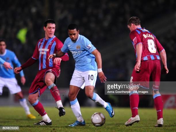 Manchester City's De Souza Robinho battles his way past Scunthorpe United's Grant McCann and Cliff Byrne