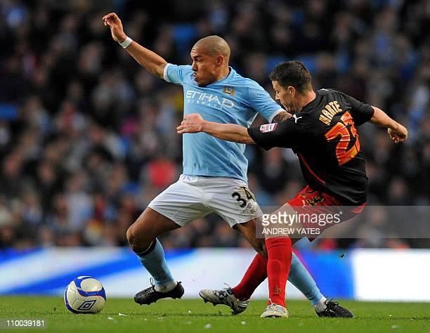 Manchester City's Dutch midfielder Nigel de Jong vies with Reading's Irish defender Ian Harte during the FA Cup quarterfinal football match between...