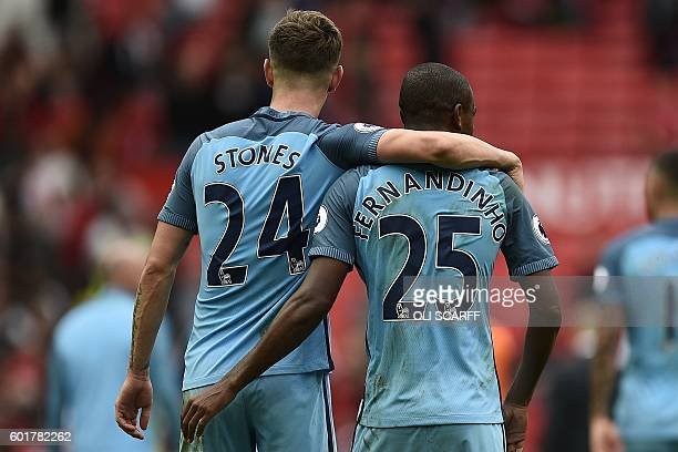 Manchester City's English defender John Stones and Manchester City's Brazilian midfielder Fernandinho celebrate on the pitch after the English...