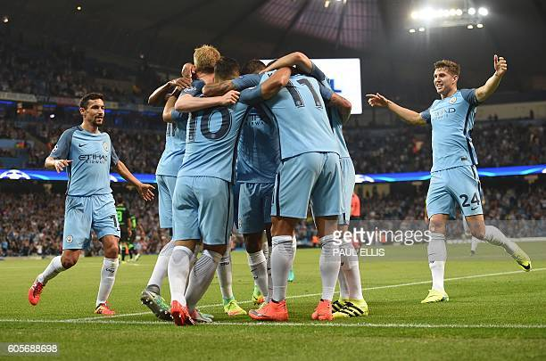 Manchester City's English defender John Stones and Manchester City's Spanish midfielder Jesus Navas join the celebration after Manchester City's...