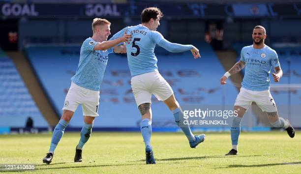 Manchester City's English defender John Stones celebrates scoring his team's second goal with Manchester City's Ukrainian midfielder Oleksandr...