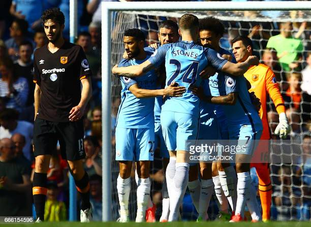 Manchester City's English defender John Stones celebrates with teammates after Hull City's Egyptian midfielder Ahmed Elmohamady scored the opening...