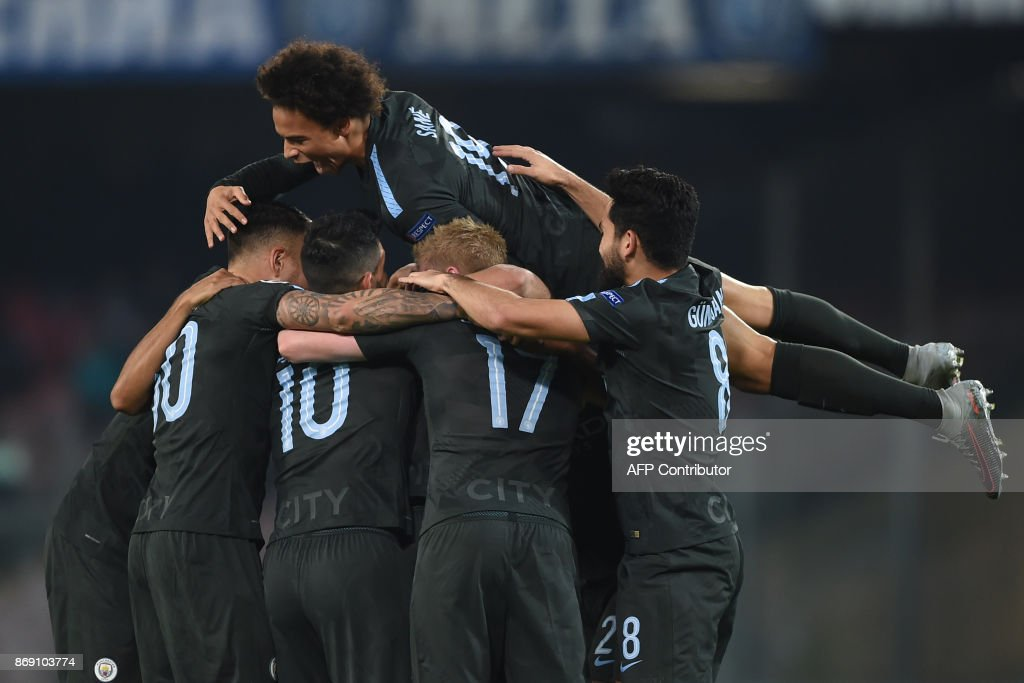 Manchester City's English defender John Stones (hidden) celebrates with teammates after scoring during the UEFA Champions League football match Napoli vs Manchester City on November 1, 2017 at the San Paolo stadium in Naples. Manchester City won 2-4. / AFP PHOTO / Filippo MONTEFORTE