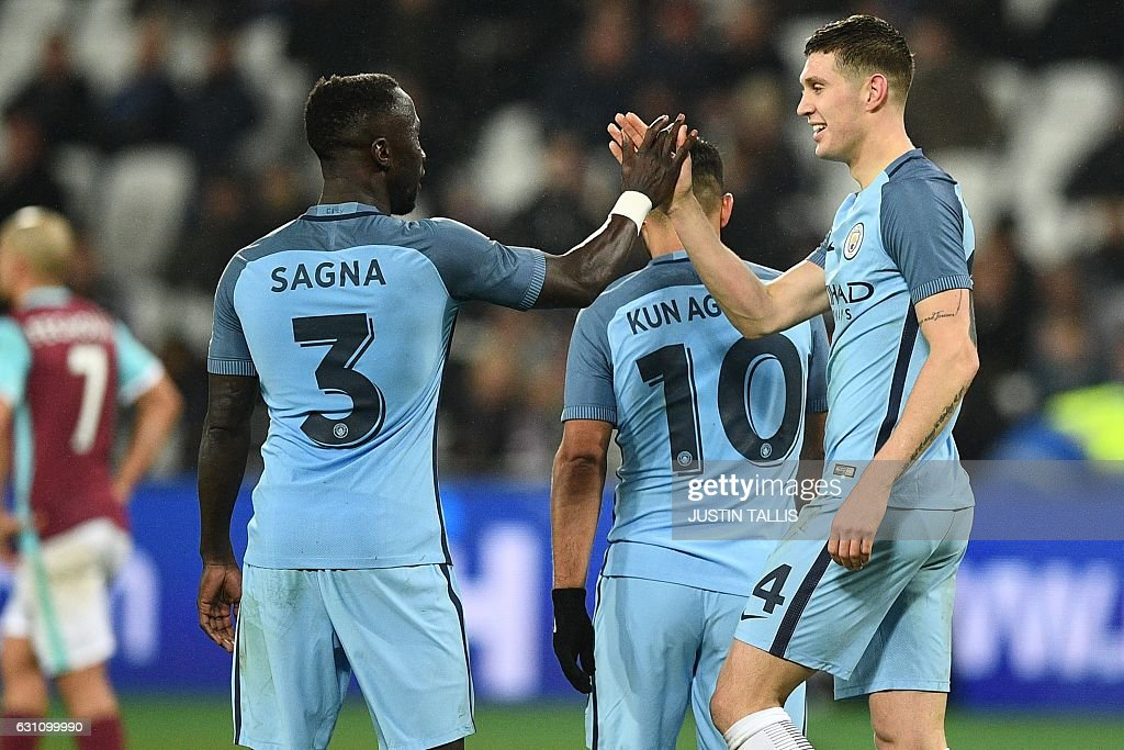 Manchester City's English defender John Stones celebrates with Manchester City's French defender Bacary Sagna after scoring their fifth goal during the English FA cup third round football match between West Ham United and Manchester City at the London Stadium in east London on January 6, 2017. Manchester City won the game 5-0. / AFP / Justin TALLIS / RESTRICTED TO EDITORIAL USE. No use with unauthorized audio, video, data, fixture lists, club/league logos or 'live' services. Online in-match use limited to 75 images, no video emulation. No use in betting, games or single club/league/player publications. /