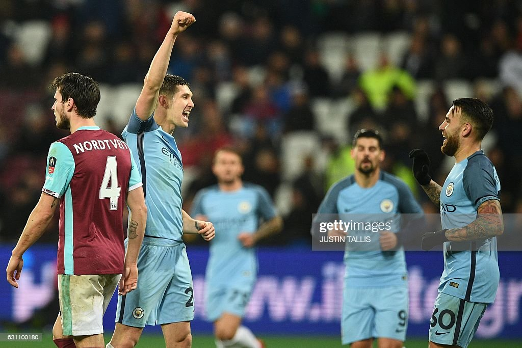 Manchester City's English defender John Stones (2nd L) celebrates with Manchester City's Argentinian defender Nicolas Otamendi (R) after scoring their fifth goal during the English FA cup third round football match between West Ham United and Manchester City at the London Stadium in east London on January 6, 2017. Manchester City won the game 5-0. / AFP / Justin TALLIS / RESTRICTED TO EDITORIAL USE. No use with unauthorized audio, video, data, fixture lists, club/league logos or 'live' services. Online in-match use limited to 75 images, no video emulation. No use in betting, games or single club/league/player publications. /