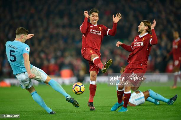 Manchester City's English defender John Stones clears the ball from Liverpool's Brazilian midfielder Roberto Firmino and Liverpool's English...