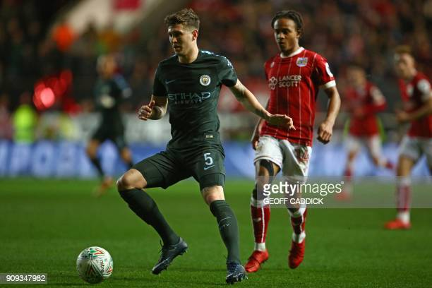 Manchester City's English defender John Stones controls the ball under pressure from Bristol City's English striker Bobby Reid during the English...
