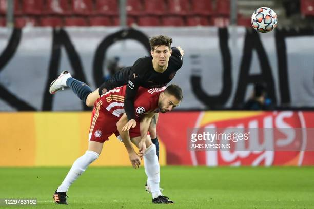 Manchester City's English defender John Stones fights for the ball with Olympiakos' Greek midfielder Kostas Fortounis during the UEFA Champions...