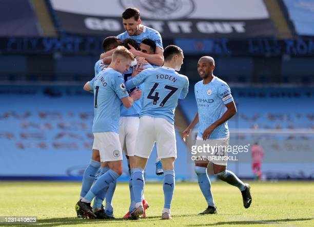 Manchester City's English defender John Stones is mobbed by teammates after scoring their second goal during the English Premier League football...