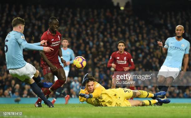 Manchester City's English defender John Stones kicks the ball against Manchester City's Brazilian goalkeeper Ederson nearly causing an owngoal during...