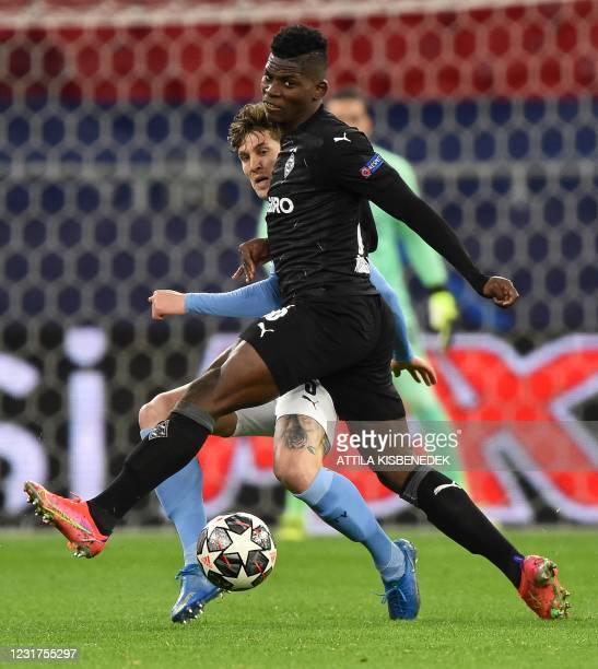 Manchester City's English defender John Stones vies with Borussia Moenchengladbach's Swiss forward Breel Embolo during the UEFA Champions League,...
