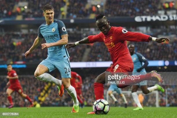 TOPSHOT Manchester City's English defender John Stones watches Liverpool's Senegalese midfielder Sadio Mane during the English Premier League...