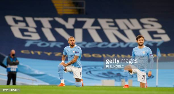 Manchester City's English defender Kyle Walker and Manchester City's Portuguese midfielder Bernardo Silva take a knee before kick off to show support...