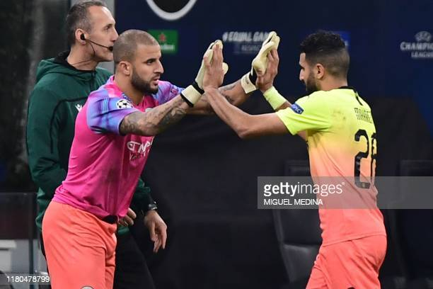 Manchester City's English defender Kyle Walker taps hands with Manchester City's Algerian midfielder Riyad Mahrez as he enters the pitch as a...