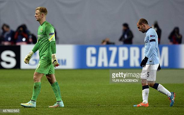 Manchester City's English goalkeeper Joe Hart and Manchester City's Argentinian defender Pablo Zabaleta walk off the pitch at the end of the UEFA...
