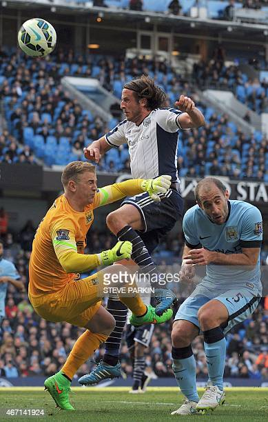 Manchester City's English goalkeeper Joe Hart and Manchester City's Argentinian defender Pablo Zabaleta clash with West Bromwich Albion's Swedish...