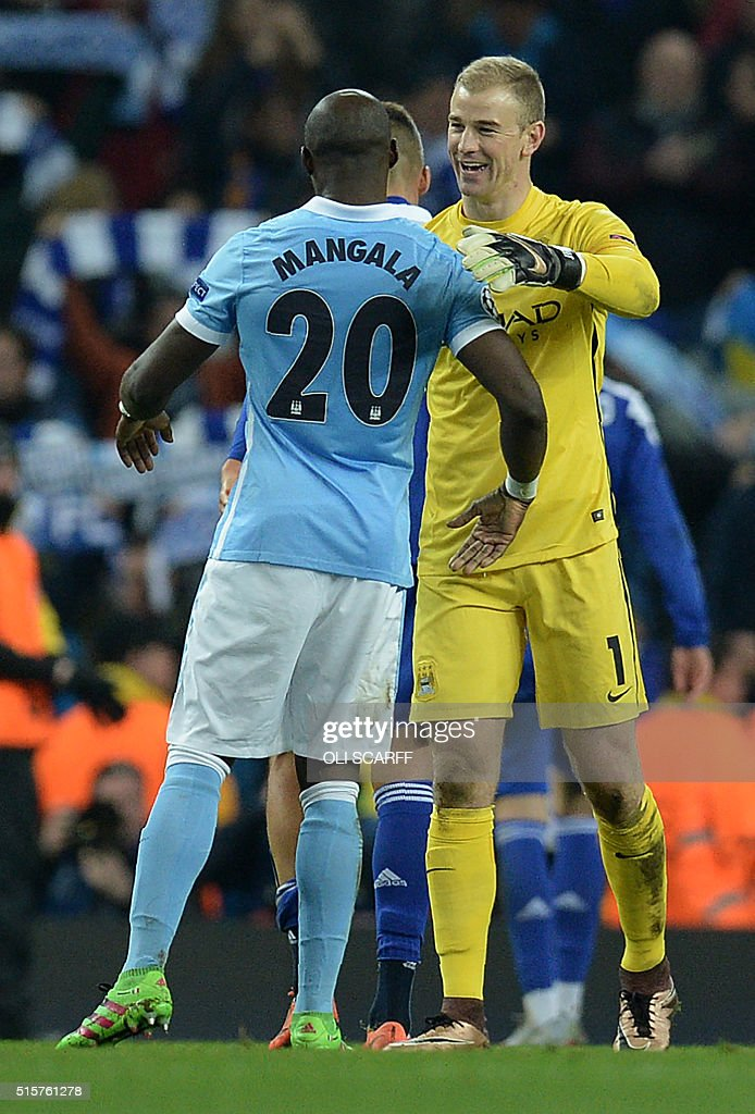 Manchester City's English goalkeeper Joe Hart (R) congratulates Manchester City's French defender Eliaquim Mangala following a UEFA Champions League last 16, second leg football match between Manchester City and Dynamo Kiev at the Etihad Stadium in Manchester, north west England, on March 15, 2016. The match ended in a draw. / AFP / OLI