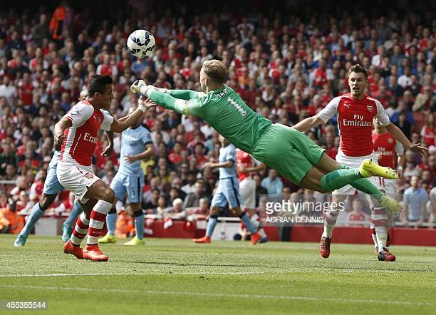 Manchester City's English goalkeeper Joe Hart punches the ball away from in front of Arsenal's Chilean striker Alexis Sanchez during the English...