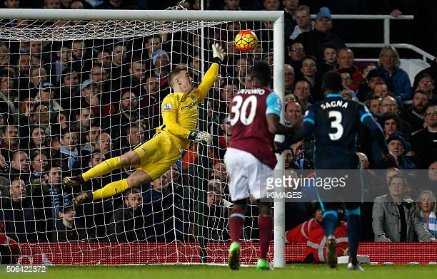 Manchester City's English goalkeeper Joe Hart saves a shot from a free kick by West Ham United's French midfielder Dimitri Payet during the English...