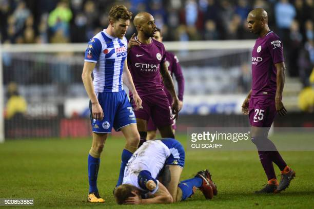 Manchester City's English midfielder Fabian Delph and Manchester City's Brazilian midfielder Fernandinho look on after tackle on Wigan Athletic's...