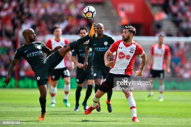 Manchester City's English midfielder Fabian Delph and Southampton's English striker Charlie Austin go for the ball during the English Premier League...