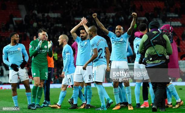 Manchester City's English midfielder Fabian Delph celebrates with teammates at the end of the English Premier League football match between...