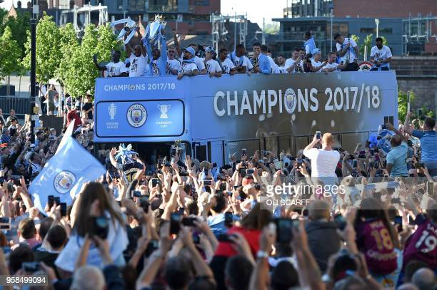 Manchester City's English midfielder Fabian Delph holds up the Preimer League trophy as Manchester City's Belgian defender Vincent Kompany holds up...