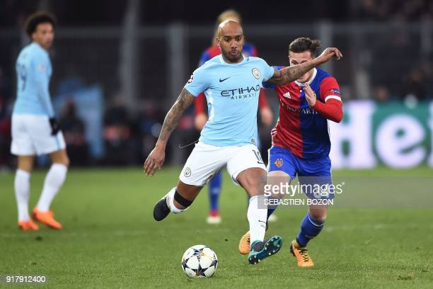 Manchester City's English midfielder Fabian Delph vies for the ball with Basel's Albanian midfielder Taulant Xhaka during the UEFA Champions League...