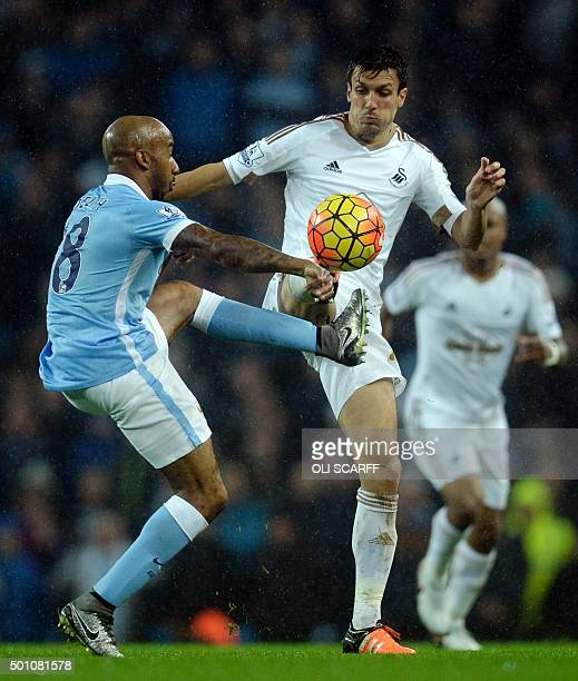Manchester City's English midfielder Fabian Delph vies with Swansea City's English midfielder Jack Cork during the English Premier League football...