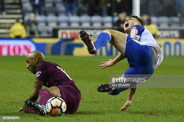 Manchester City's English midfielder Fabian Delph's tackle on Wigan Athletic's English midfielder Max Power leads to a red card during the English FA...