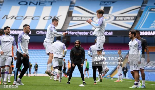 Manchester City's English midfielder Phil Foden and Manchester City's English defender John Stones warm up ahead of the English Premier League...