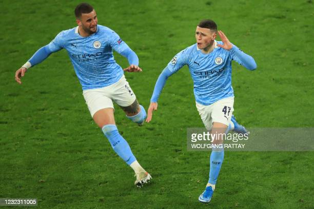 Manchester City's English midfielder Phil Foden celebrates scoring the 1-2 goal with his team-mate Manchester City's English defender Kyle Walker...
