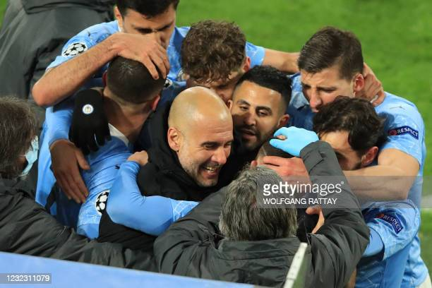 Manchester City's English midfielder Phil Foden celebrates scoring the 1-2 goal with his team-mates and Manchester City's Spanish manager Pep...
