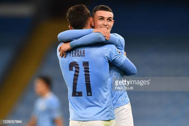 Manchester City's English midfielder Phil Foden embraces Manchester City's Spanish midfielder Ferran Torres on the pitch after the UEFA Champions...
