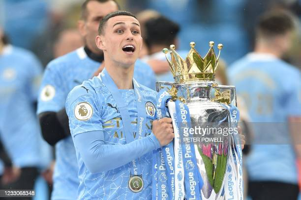 Manchester City's English midfielder Phil Foden lifts the Premier League trophy during the award ceremony after the English Premier League football...