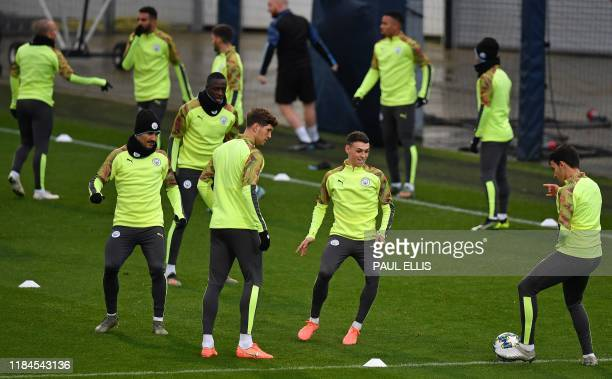 Manchester City's English midfielder Phil Foden Manchester City's English defender John Stones and Manchester City's German midfielder Ilkay Gundogan...