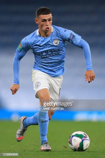 Manchester City's English midfielder Phil Foden runs with the ball during the English League Cup third round football match between Manchester City...