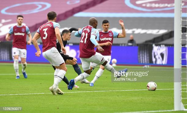 Manchester City's English midfielder Phil Foden scores the equalising goal during the English Premier League football match between West Ham United...