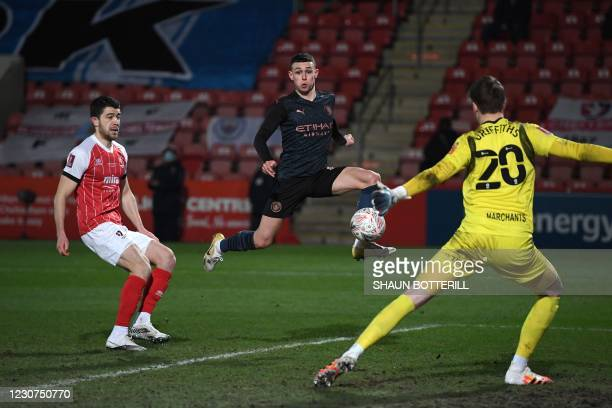 Manchester City's English midfielder Phil Foden shoots to score their first goal during the English FA Cup fourth round football match between...