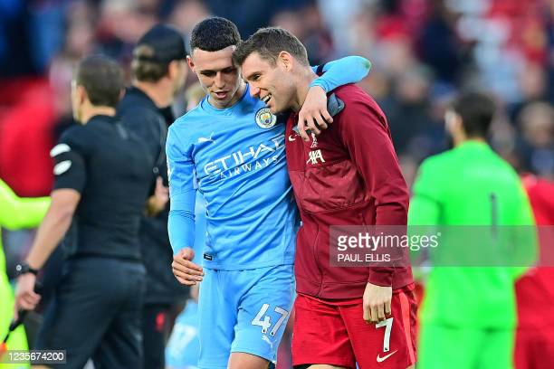 Manchester City's English midfielder Phil Foden speaks with Liverpool's English midfielder James Milner at the end of the English Premier League...