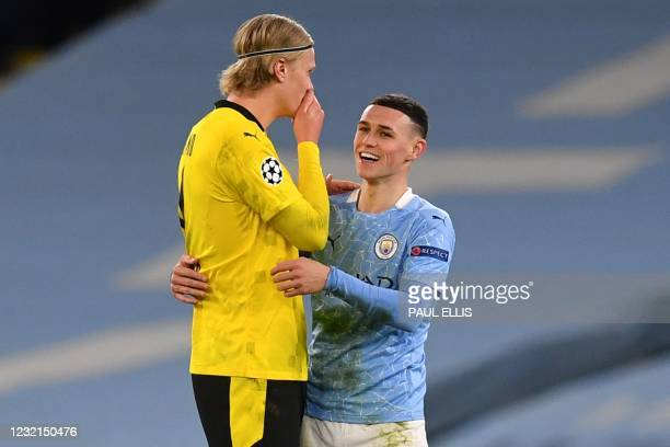 Manchester City's English midfielder Phil Foden walks off the pitch with Dortmund's Norwegian forward Erling Braut Haaland after the UEFA Champions...