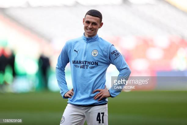 Manchester City's English midfielder Phil Foden warms up ahead of the English League Cup final football match between Manchester City and Tottenham...