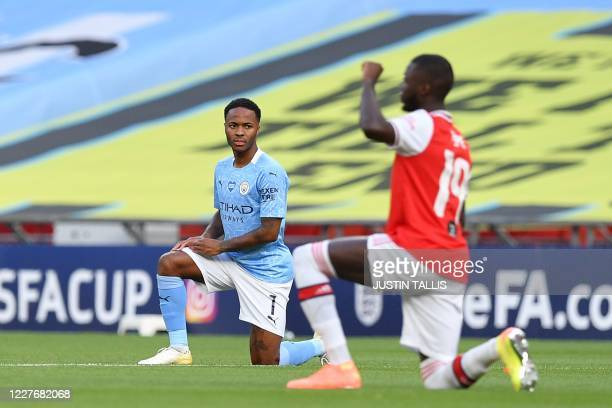 Manchester City's English midfielder Raheem Sterling and Arsenal's Frenchborn Ivorian midfielder Nicolas Pepe take a knee to support the Black Lives...