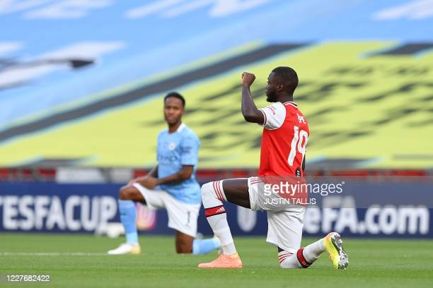 Manchester City's English midfielder Raheem Sterling and Arsenal's French-born Ivorian midfielder Nicolas Pepe take a knee to support the Black Lives...