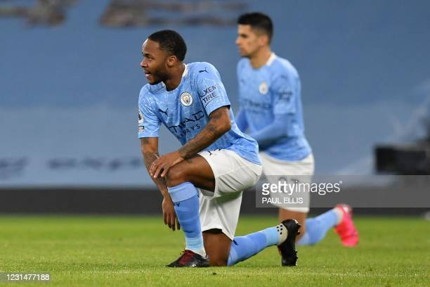 Manchester City's English midfielder Raheem Sterling and Manchester City's Portuguese defender Joao Cancelo take the knee in support of the No Room...