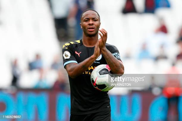 Manchester City's English midfielder Raheem Sterling applauds as he carries the match ball after scoring a hatttick to help his team win 50 during...