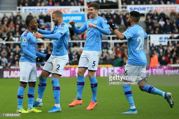 Manchester City's English midfielder Raheem Sterling celebrates with teammates after scoring his team's first goal during the English Premier League...
