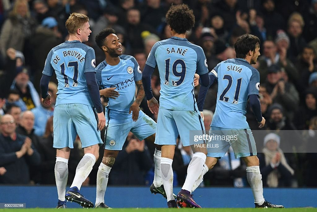 Manchester City's English midfielder Raheem Sterling (2nd L) celebrates with teammates after scoring their second goal during the English Premier League football match between Manchester City and Arsenal at the Etihad Stadium in Manchester, north west England, on December 18, 2016. / AFP / Paul ELLIS / RESTRICTED TO EDITORIAL USE. No use with unauthorized audio, video, data, fixture lists, club/league logos or 'live' services. Online in-match use limited to 75 images, no video emulation. No use in betting, games or single club/league/player publications. /