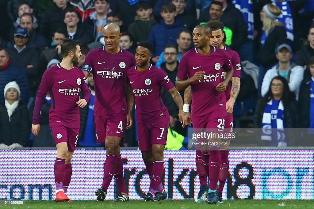 Manchester City's English midfielder Raheem Sterling (C) celebrates with teammates after scoring their second goal during the English FA Cup fourth round football match between Cardiff City and Manchester City at Cardiff City Stadium in Cardiff, south Wales on January 28, 2018. / AFP PHOTO / Geoff CADDICK / RESTRICTED TO EDITORIAL USE. No use with unauthorized audio, video, data, fixture lists, club/league logos or 'live' services. Online in-match use limited to 75 images, no video emulation. No use in betting, games or single club/league/player publications. /