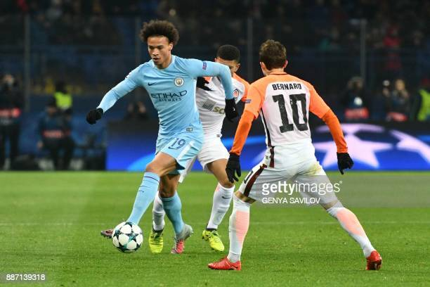 Manchester City's English midfielder Raheem Sterling drives the ball next to Shakhtar Donetsk's Brazilian midfielder Bernard during the UEFA...